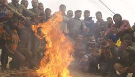 People gather around a fire during a winter morning in Dhaka.