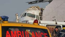 Emergency personnel are seen at the site of a plane crash near Almaty, Kazakhstan