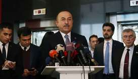 Turkish Foreign Minister Mevlut Cavusoglu (C) holds a press conference after his meeting with Chairm