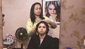 In this picture taken on October 15, 2019, transgender beautician Bebo Haider attends to a customer