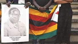 Mourners hold a poster during the state funeral of Zimbabwe's longtime ruler Robert Mugabe at a nati