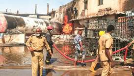 Members of the Sudanese Civil Defence put out a fire at a tile manufacturing unit in an industrial z