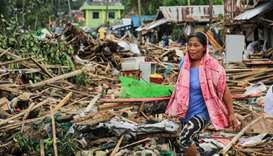 A resident walks past debris from their destroyed houses after Typhoon Kammuri hit the city of Sorso