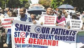 Doctors hold banners during a protest march in Harare, yesterday.