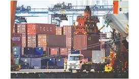 A worker stands next to a truck as a gantry crane moves a container at a shipping terminal in Yokoha