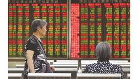 Women talk in front of a screen showing stock prices at a securities company in Beijing. Shanghai bo