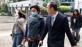 Tsang Chi-Kin (centre), who was shot by a police officer during a protest, arrives for a court heari