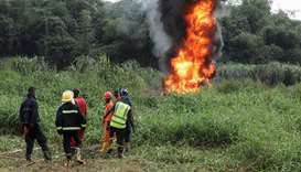 Firefighters and safety officers are seen in the Lagos swamp of Baruwa, where a burst oil pipeline i