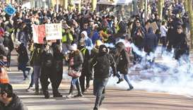 Protesters run to avoid tear gas smoke during a demonstration in Bordeaux against the government's p