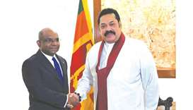 Sri Lanka's Prime Minister Mahinda Rajapaksa, right, shakes hands with Maldives' Foreign Minister Ab