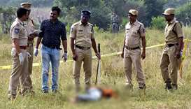 Police personnel stand next to the body of a man at the site where Police officers shot dead four de