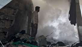 A man stands before a cloud of dust amidst rubble in a collapsed building following a reported air s