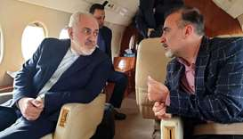 Iranian Foreign Minister's official Twitter account shows Foreign Minister Mohammad Javad Zarif (L)