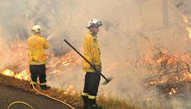 Firefighters conduct back burning measures to secure residential areas from encroaching bushfires at