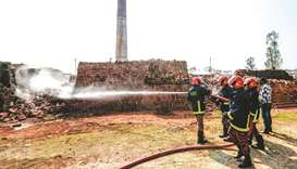 Firefighters spray water over a brick kiln as local authorities prepare to demolish illegal brick ki