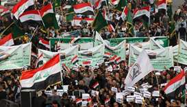 Iraqi demonstrators wave national flags and carry banners as the take part in an anti-government dem