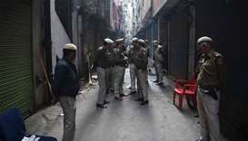 Police personnel stand on a street near a factory site where a fire broke out a day before, in Anaj