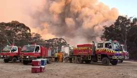 Smoke of fire rise next to firefighting vehicles as bushfires burn in Newnes Plateau, New South Wall