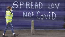 A pedestrian walks past graffiti reading 'Spread (love), not Covid' on the shutters of a closed shop