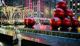 A woman walks around Christmas decorations as the global outbreak of the coronavirus disease (Covid-