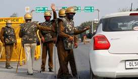Police officers in riot gear check a car for protesting farmers at a state border on a national high