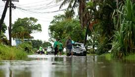 Residents wade through the flooded streets in Fiji's capital city of Suva
