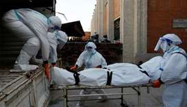 Female soldiers wearing personal protective equipment (PPE) load a body of a coronavirus victim insi