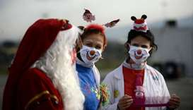 Medical workers dressed as clowns and Santa Claus entertain people lined up in their car to undergo