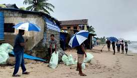 Residents prepare sand bags to protect their homes ahead of cyclone Burevi landfall in Sri Lanka's n