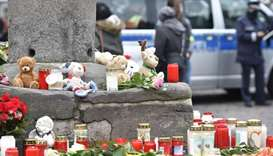 Candles and flowers are placed at a makeshift memorial for the victims at the market column at Haupt
