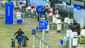 A traveller walks with luggage to the United Airlines Holdings check-in counter at San Francisco Int