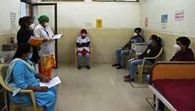 Health workers sit inside an observation room at the Public Health Centre (PHC) in Adalaj