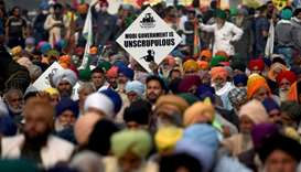 Farmers listen to a speaker as they take part in a protest against the central government's recent a