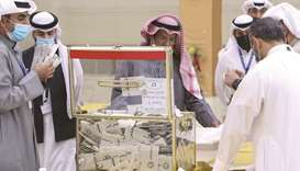 A Kuwaiti judge (centre) and his aides count the ballots at a polling station at the end of the parl