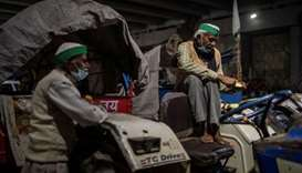 A farmers rests on his tractor parked on a blocked highway during a protest against the newly passed