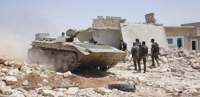 Syrian army soldiers walk in Bureij village of Aleppo province yesterday, after claiming to have adv