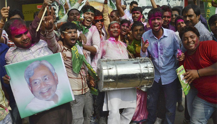 Supporters of the Janata Dal (United) party celebrate after learning of the initial election results