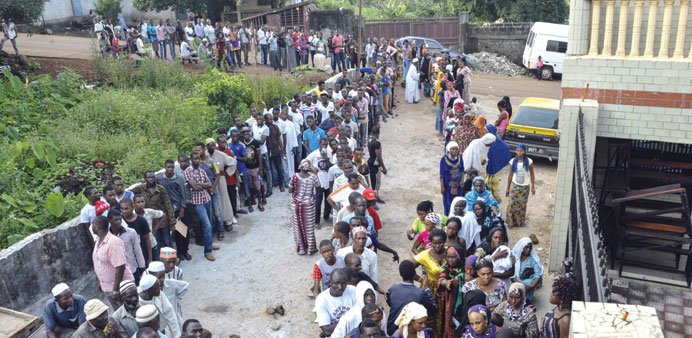 Voters queue at a polling station in Conakry yesterday.