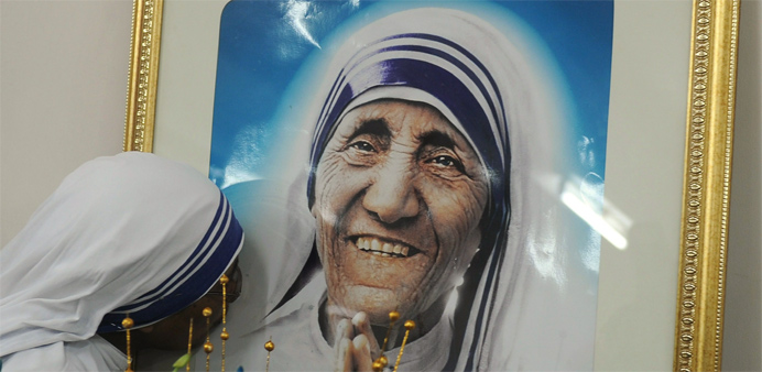 A nun belonging to the order of the Missionaries of Charity kisses a picture of Mother Teresa