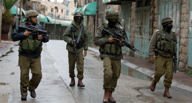 Israeli soldiers patrol near the Jewish settlement of Beit Hadassah in the Israeli-occupied city of