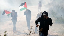 Palestinian protesters, some holding national flags, run away from tear gas smoke