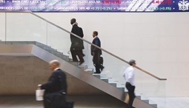 People walk past an electronic information board at the London Stock Exchange. London equities fell