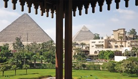 The ancient pyramids of Giza stand beyond the gardens of the Mena House hotel in Cairo. Tourism gene