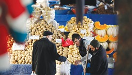 A vendor sells potatoes and other vegetables to a customer in an open market in central Ankara. The