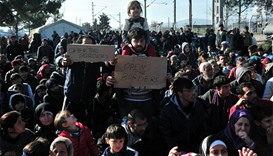 Men hold banners as migrants demonstrate as they wait to cross the Greece Macedonian border