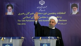 Iranian President Hassan Rouhani waves after casting his vote