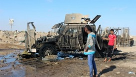 Yemenis inspect a burnt armored vehicle after a suicide bomber rammed his explosives-laden vehicle i