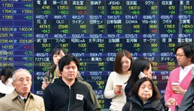 Pedestrians walk past a share prices board in Tokyo. The Nikkei 225 closed down 3.2% at 17,191.25 po