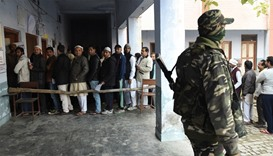 Indian security personnel stands guard as voters queue to cast their vote