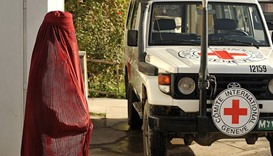 Afghan pedestrain walks past a vehicle at the International Committee for the Red Cross